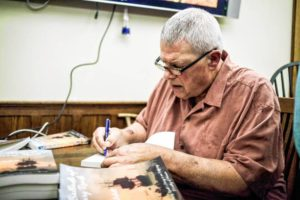 Local Author Norman Schell signs books for patrons after a rousing reading.